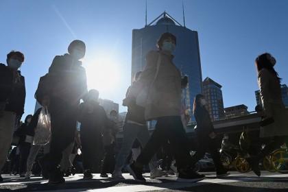 People walk along a street in Beijing, China, on 12 October 2021. (Noel Celis/AFP)