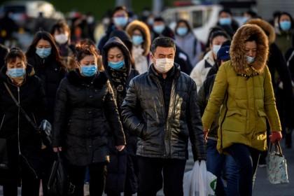 People wearing face masks walk along astreetduring a rush hour in Bejing on 16 December 2020. (Noel Celis/AFP)