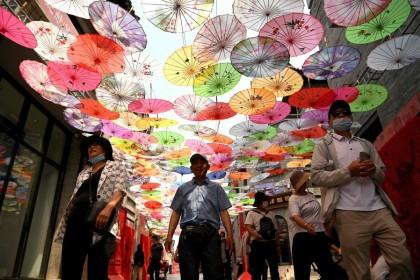 People walk along Qianmen street in Beijing on 19 May 2021. (Noel Celis/AFP)
