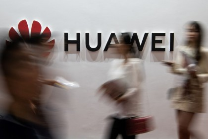 People walk past a Huawei logo during the Consumer Electronics Expo in Beijing in this file photo taken on 2 August 2019. (Fred Dufour/AFP)