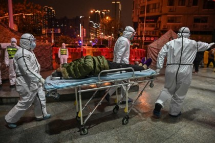 In this file photo taken on 25 January 2020, medical staff members wearing protective clothing to help stop the spread of a deadly virus which began in the city arrive with a patient at the Wuhan Red Cross Hospital in Wuhan. (Hector Retamal/AFP)