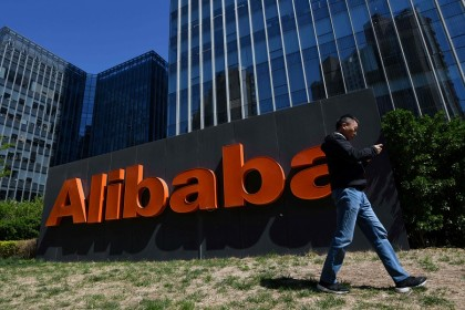 In this file photo taken on 13 April 2021, a man walks past an Alibaba sign outside the company's office in Beijing, China. (Greg Baker/AFP)