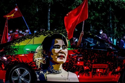 In this file photo taken on 8 November 2020, supporters of the National League for Democracy (NLD) party wave flags, with the car bearing an image of Myanmar's de facto leader Aung San Suu Kyi, in front of the party's office in Mandalay. (Ye Naing Ye/AFP)