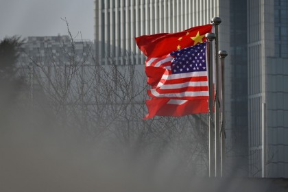 In this file photo taken on 19 January 2020, Chinese and US national flags flutter at the entrance of a company office building in Beijing. (Wang Zhao/AFP)