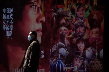 A man wearing a protective facemask stands in front of a movie poster in Shanghai. - China on February 19, 2020 ordered three reporters from American newspaper the Wall Street Journal to leave the country over what Beijing deemed a racist headline, in one of the harshest moves against foreign media in years. (Noel Celis/AFP)