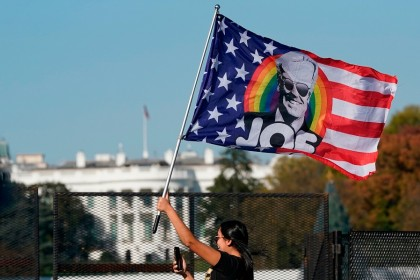 In this file photo taken on 7 November 2020, a woman waves a Joe Biden flag as people celebrate on Black Lives Matter Plaza across from the White House in Washington, DC, after Biden was declared the winner of the 2020 presidential election. (Alex Edelman/AFP)