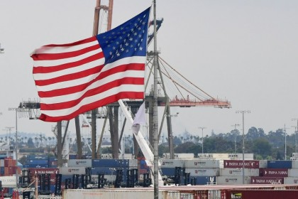 In this file photo the US flag flies in the foreground as containers are seen at the Port of Los Angeles on 18 June 2019 in San Pedro, California. Spending by American consumers and record-high imports as the global economy reopened drove the US trade gap to a new all-time high in March, the Commerce Department reported on 4 May 2021. The trade deficit rose 5.6% to US$74.4 billion, the highest ever recorded and mostly attributable to trade with China. (Frederic J. Brown/AFP)