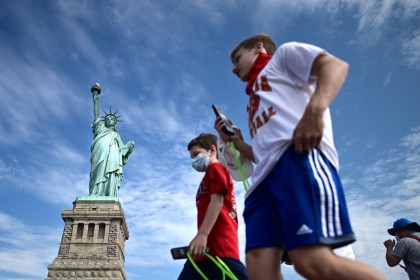 In this file photo tourists wearing facemasks walk on the reopened Liberty Island in front of the Statue of Liberty on 20 July 2020 in New York City. (Johannes Eisele/AFP)