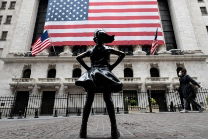 The fearless girl statue and the New York Stock Exchange (NYSE) are pictured on 20 April 2020 at Wall Street in New York City. (Johannes Eisele/AFP)