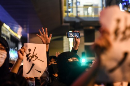 "People chant slogans and hold the words ""release (the protesters)"" near a police-cordoned area to show support for a small group of protesters barricaded for over a week inside the Hong Kong Polytechnic University campus in Hung Hom district in Hong Kong on November 25, 2019. (Ye Aung Thu/AFP)"