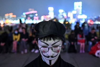 A protester wears the Guy Fawkes mask during a prayer rally in Tamar Park in Hong Kong on November 9, 2019, in memory of university student Alex Chow. (Philip Fong/AFP)