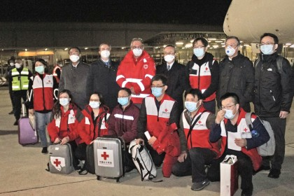This photo provided by Italian news agency Ansa on 13 March 2020 shows Chinese medics posing for a group photo after landing on a China Eastern flight on 13 March at Rome's Fiumicino international airport from Shanghai, bringing medical aid to help fight the new coronavirus in Italy. (STRINGER/ANSA/AFP)