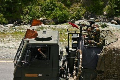 Indian army soldiers ride in a convoy along a highway leading towards Leh, bordering China, in Gagangir on 17 June 2020. (Tauseef Mustafa/AFP)