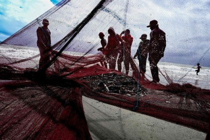 Fishermen pull in their net along the coast of Banda Aceh on 1 August 2021. (Chaideer Mahyuddin/AFP)