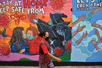 An Indonesian woman walks past a mural created by Indonesian artist Bayu Rahardian amid the Covid-19 coronavirus pandemic in Depok on 16 April 2020. (Adek Berry/AFP)