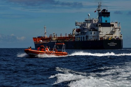 A dinghy (left) from Indonesia's National Search And Rescue Agency (BASARNAS) returns to their vessel after evacuating a Russian crew member from the Danish tanker Hulda Maersk (right) for medical reasons, at sea off the coast of Aceh on 27 April 2021. (Chaideer Mahyuddin/AFP)