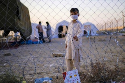 A handout picture made available by the Iranian Red Crescent on 19 August 2021, shows a young Afghan refugee at the Iran-Afghanistan border between Afghanistan and the southeastern Iranian Sistan and Baluchestan province, as people fleeing AFghanistan try to enter the Islamic republic following the takeover of their country by the Taliban earlier this week. (Mohammad Javadzadeh/Iranian Red Crescent/AFP)