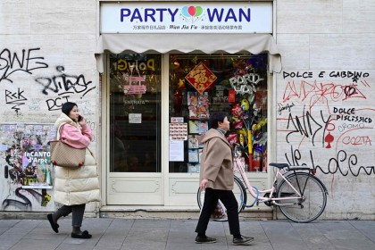 Passers-by pass by a shop in Via Paolo Sarpi, the commercial street of the Chinese district of Milan on 30 January 2020. (Miguel Medina/AFP)