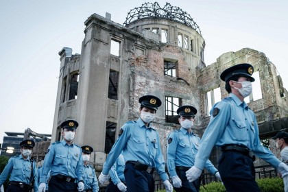 In this photo taken on 6 August 2021, police officers walk beside the Hiroshima Prefectural Industrial Promotion Hall, as it was known before 1945 and now called the Atomic Bomb Dome, as the city marks the 76th anniversary of the world's first atomic bomb attack. (Yasuyoshi Chiba/AFP)
