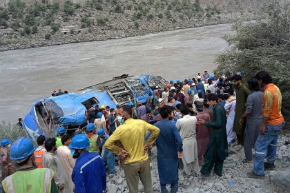 Rescue workers and onlookers gather around a wreck after a bus plunged into a ravine following a bomb explosion, which killed 13 people including nine Chinese workers, in the Kohistan district of Khyber Pakhtunkhwa province, Pakistan on 14 July 2021. (STR/AFP)