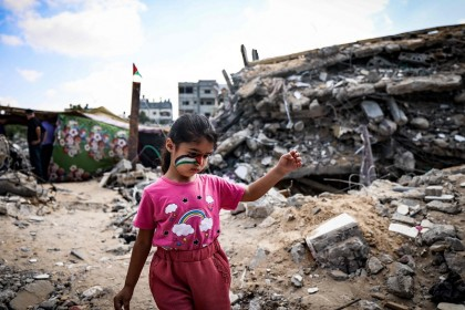 A Palestinian girl plays amidst the rubble of buildings destroyed by last month's Israeli bombardment of the Gaza Strip, in Beit Lahia, in the northern part of the Palestinian enclave on 19 June 2021. (Mahmud Hams/AFP)
