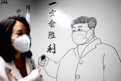 A woman walks in front of a drawing of Chinese President Xi Jinping on a wall at the Leishenshan Hospital that had offered beds for coronavirus patients in Wuhan, April 11, 2020. (Noel Celis/AFP)