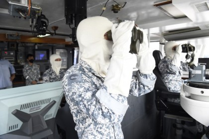 A crew member on the RSS Vigour acting as the lookout at the bridge as the team investigates a potential contact of interest. (MINDEF)