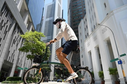 A man rides a bicycle along a street at the Raffles Place financial business district in Singapore on 20 April 2021. (Roslan Rahman/AFP)