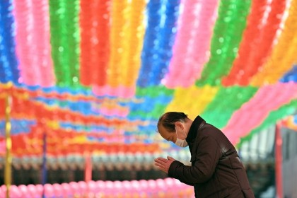 A Buddhist follower wearing a face mask prays under rows of lotus lanterns ahead of Buddha's birthday at Jogyesa Temple in Seoul on 23 March 2020. (Jung Yeon-je/AFP)