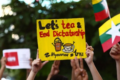 "Myanmar migrants in Thailand holds signs relating to the ""Milk Tea Alliance"" as they take part in a protest in Bangkok on 28 February 2021, against the military coup in their home country. (Jack Taylor/AFP)"