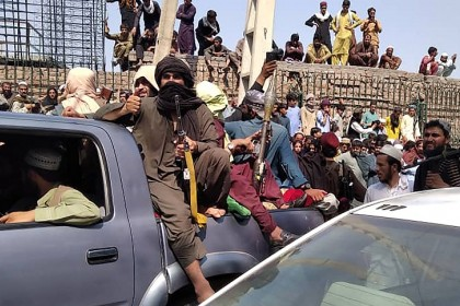 Taliban fighters sit on a vehicle along the street in Jalalabad province, Afghanistan on 15 August 2021. (AFP)