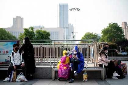 People wearing face masks sit outside Hankou Railway Station in Wuhan in hopes of taking one of the first trains leaving the city early on 8 April 2020. (Noel Celis/AFP)