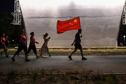 In this photo taken on 4 September 2020, a man walks with the Chinese national flag in a park next to the Yangtze River in Wuhan. (Hector Retamal/AFP)