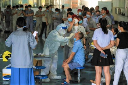 A worker receives a nucleic acid test for the Covid-19 coronavirus at the dining hall of a car parts factory in Wuhan, in China's central Hubei province on 4 August 2021. (STR/AFP)