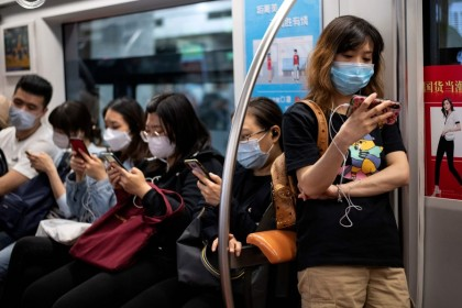 Passengers use their mobile phones on the subway in Beijing, 12 May 2020. (Noel Celis/AFP)