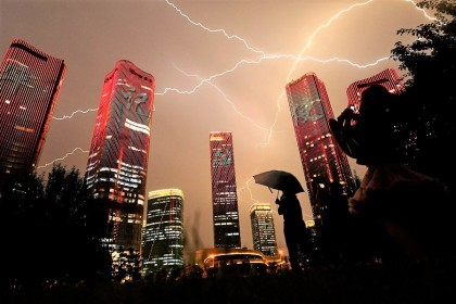 A bolt of lightning crosses the sky as people look at buildings displaying a light show on the eve of the 100th anniversary of the Chinese Communist Party in Beijing, China, on 30 June 2021. (Noel Celis/AFP)