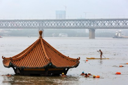 People (foreground) swim in the swollen Yangtze River as the roof of an inundated pavilion is seen above floodwaters in Wuhan, Hubei, on 8 July 2020. (STR/AFP)