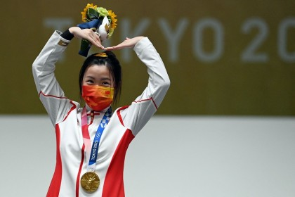 China's Yang Qian celebrates on the podium after winning the women's 10m air rifle final during the Tokyo 2020 Olympic Games at the Asaka Shooting Range in the Nerima district of Tokyo, Japan, on 24 July 2021. (Tauseef Mustafa/AFP)