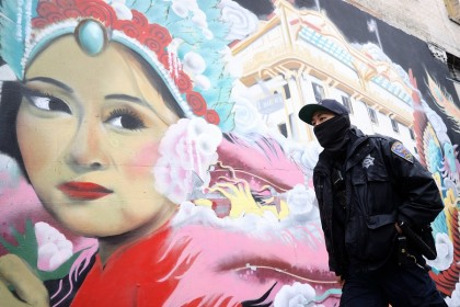 A police officer walks by a mural while on a foot patrol in Chinatown on 18 March 2021 in San Francisco, California. (Justin Sullivan/Getty Images/AFP)