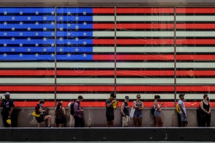 People queue to board a tourist bus before a display showing a US flag in Times Square in New York City, US on 30 July 2021. (Ed Jones/AFP)