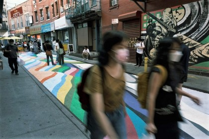 People walk on the historic Doyers Street in Chinatown that has been painted over by Chilean-born street artist Dasic Fernandez, 24 June 2021 in New York City, US. (Spencer Platt/Getty Images/AFP)