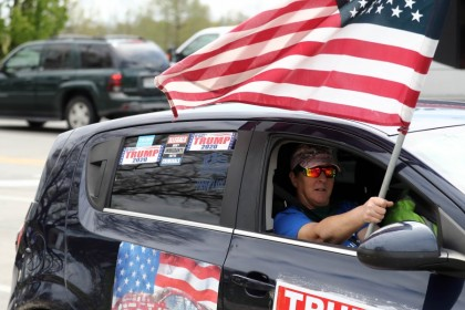 "A Trump supporter waves an American flag during a protest at the Country Club Plaza against social distancing measures, April 20, 2020 in Kansas City, Missouri. The US state of Missouri has sued China's leadership over the coronavirus, prompting an angry rebuke from Beijing April 22, 2020 over the ""absurd"" claim. Missouri is seeking damages over what it described as deliberate deception and insufficient action to stop the pandemic. (Jamie Squire/AFP)"