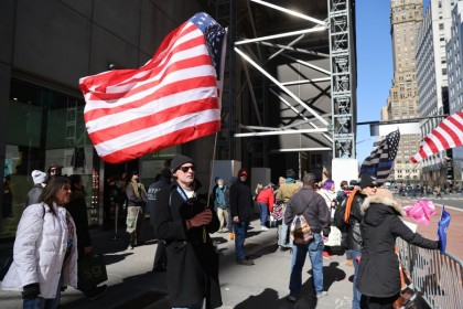 A man holds a US flag in front of Trump Tower on 8 March 2021 in New York City. (Spencer Platt/AFP)