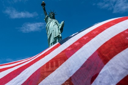 The Statue of Liberty is seen over a wind blown American flag scarf on Liberty Island on 20 July 2020 in New York City. (Jeenah Moon/Getty Images/AFP)