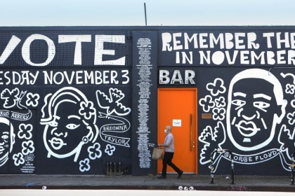 A man walks past a mural by artist Eric Junker which reads 'Vote- Remember Them In November' on 2 October 2020 in Los Angeles, California. The mural features images of deceased Black shooting victims George Floyd, Breonna Taylor and Ahmaud Arbery. (Mario Tama/AFP)