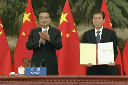 A screen grab taken from Vietnam Host Broadcaster's 15 November 2020 live video shows China's Premier Li Keqiang (L) clapping as Chinese Minister of Commerce Zhong Shan (R) holds up the agreement during the signing ceremony for the Regional Comprehensive Economic Partnership (RCEP) trade pact at the ASEAN summit that is being held online in Hanoi. (Handout/Vietnam host broadcaster/AFP)