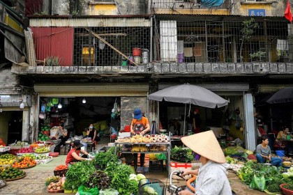 A vendor (centre) sells meat at her stall in front of a residential building in Hanoi, Vietnam on 31 March 2021. (Manan Vatsyayana/AFP)