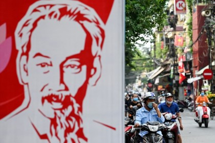 A man wearing a face mask amid Covid-19 concerns waits on his scooter near a billboard of the late Vietnamese revolutionary leader Ho Chi Minh, Hanoi, 4 May 2021. (Manan Vatsyayana/AFP)
