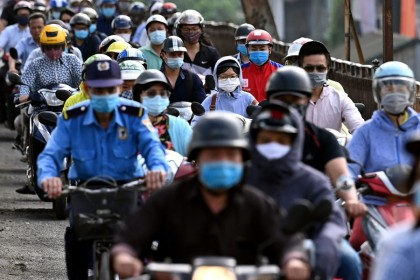 Morning commuters wearing face masks, amidst concerns about the Covid-19 coronavirus, ride past in Hanoi on 4 May 2021. (Manan Vatsyayana/AFP)