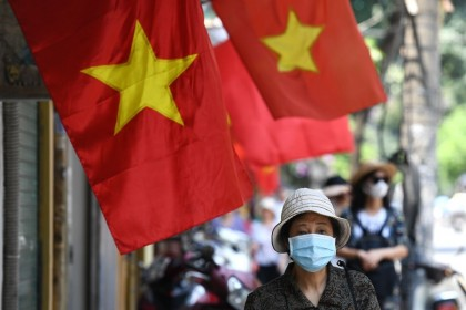 A woman walks past Vietnam national flags along a street in Hanoi, 18 May 2020. (Nhac Nguyen/AFP)